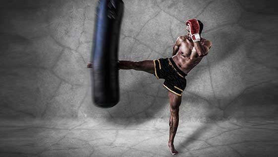 photo of muay thai madison kickboxer hitting a heavy bag